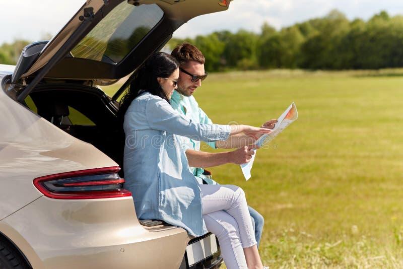 Ευτυχείς άνδρας και γυναίκα με τον οδικό χάρτη στο αυτοκίνητο hatchback στοκ εικόνες