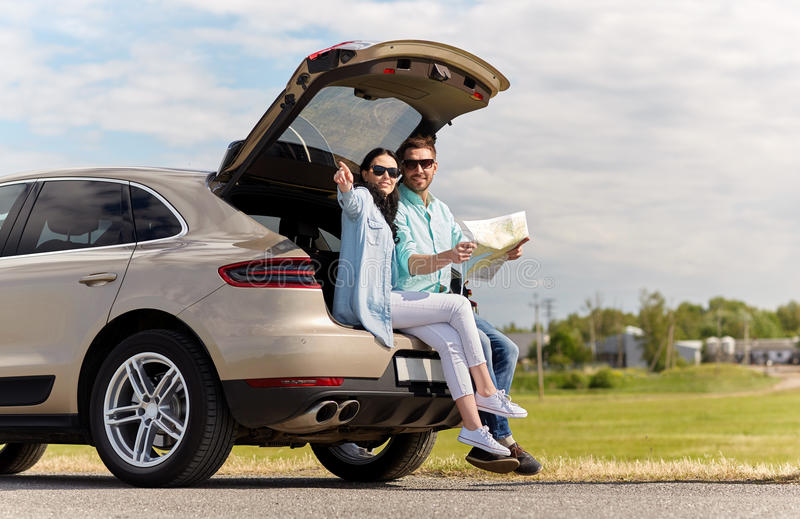Ευτυχείς άνδρας και γυναίκα με τον οδικό χάρτη στο αυτοκίνητο hatchback στοκ εικόνα