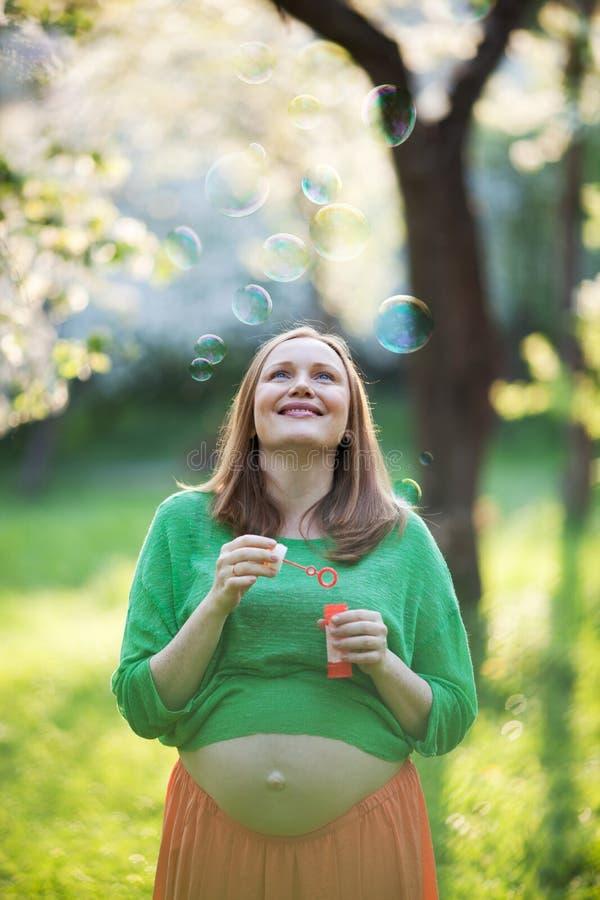 Ευτυχείς έγκυος γυναίκα και φυσαλίδες υπαίθριες στοκ φωτογραφία με δικαίωμα ελεύθερης χρήσης