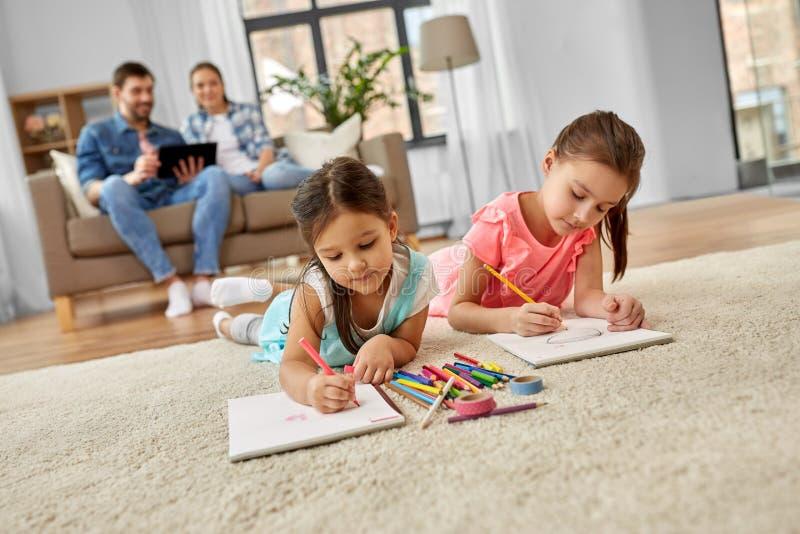Ευτυχείς αδελφές που σύρουν στα sketchbooks στο σπίτι στοκ εικόνες