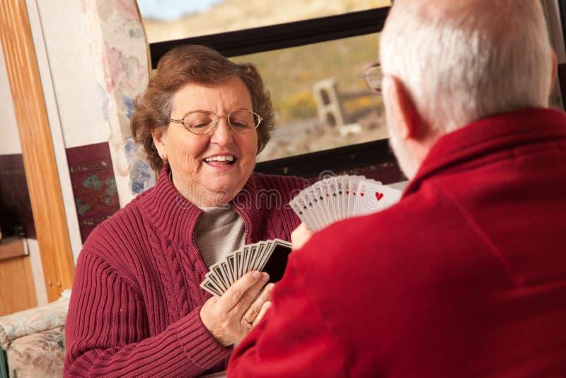 Ευτυχείς ανώτερες ενήλικες κάρτες παιχνιδιού ζεύγους στο ρυμουλκό τους rv στοκ εικόνες