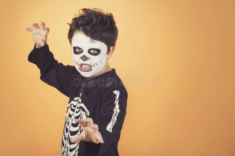 Ευτυχείς αποκριές αστείο παιδί σε ένα κοστούμι σκελετών αποκριών στοκ εικόνα
