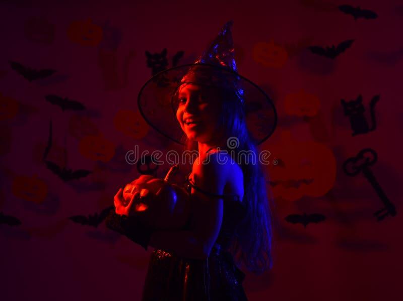 Ευτυχείς αποκριές χαριτωμένες λίγη μάγισσα με μια μεγάλη κολοκύθα στοκ φωτογραφίες