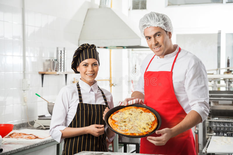 Ευτυχείς αρχιμάγειρες που παρουσιάζουν την πίτσα στην εμπορική κουζίνα στοκ φωτογραφία με δικαίωμα ελεύθερης χρήσης