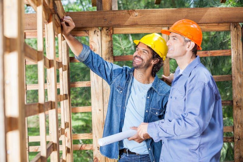 Ευτυχείς αρχιτέκτονες που συζητούν στο εργοτάξιο οικοδομής στοκ εικόνες με δικαίωμα ελεύθερης χρήσης