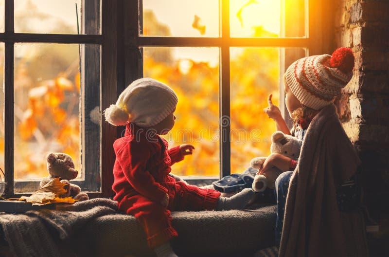 Ευτυχείς αδελφός και αδελφή παιδιών που κοιτάζουν μέσω των παραθύρων στο fal στοκ φωτογραφία με δικαίωμα ελεύθερης χρήσης