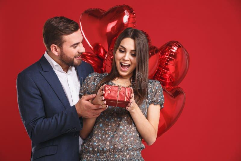 ευτυχείς βαλεντίνοι ημέ&rho Το αγόρι δίνει ένα δώρο στο κορίτσι του στοκ εικόνα