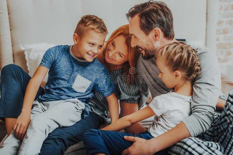 Ευτυχείς γονείς και δύο παιδιά που αγκαλιάζουν από κοινού στοκ εικόνα