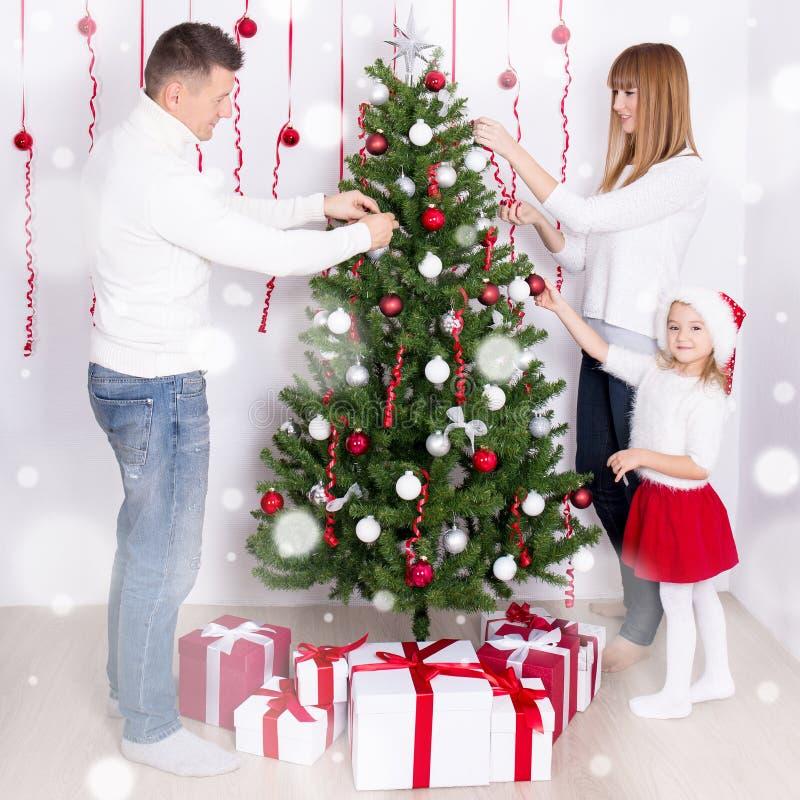 Ευτυχείς γονείς και κόρη που διακοσμούν το χριστουγεννιάτικο δέντρο στο σπίτι στοκ εικόνα
