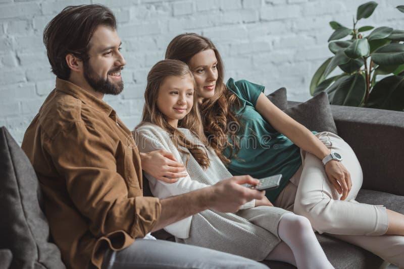 ευτυχείς γονείς και κόρη που προσέχουν τη TV στον καναπέ στοκ φωτογραφία με δικαίωμα ελεύθερης χρήσης