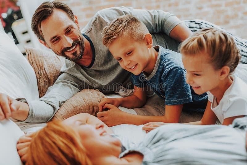 Ευτυχείς γονείς και παιδιά που χαλαρώνουν μαζί στο κρεβάτι στοκ φωτογραφίες