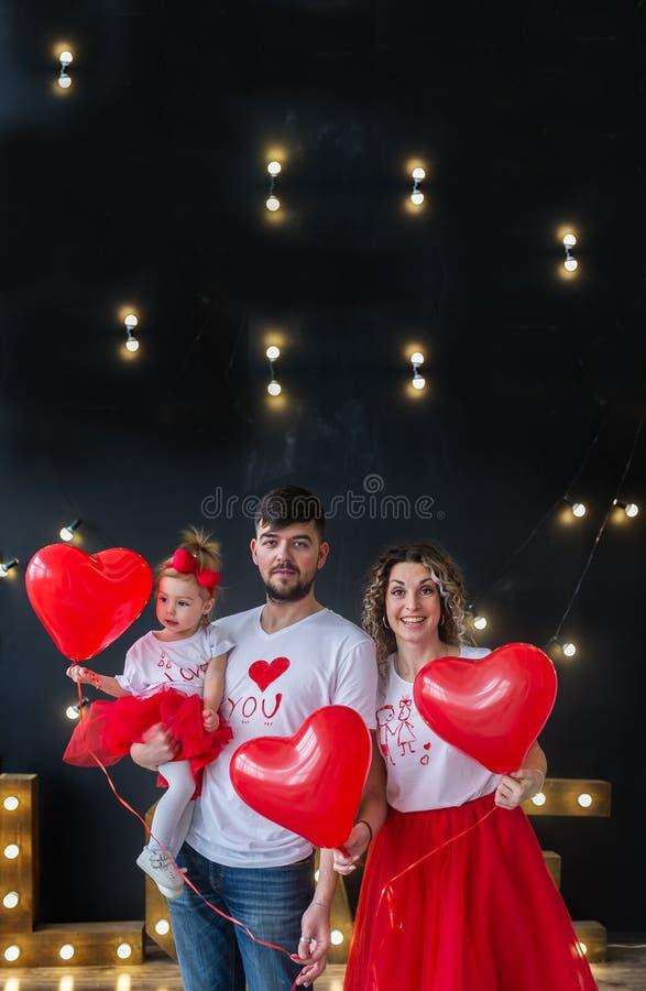 Ευτυχείς γονείς και thair κόρη μωρών την ημέρα του βαλεντίνου Αγίου Κάθετο οικογενειακό πορτρέτο στοκ εικόνα