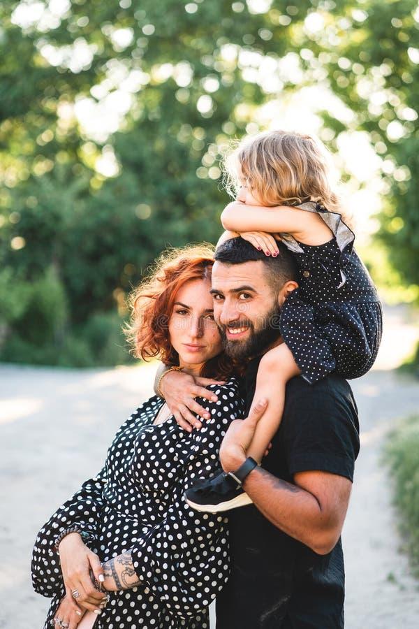 Ευτυχείς γονείς με μια μικρή συνεδρίαση κορών στους ώμους στοκ φωτογραφίες με δικαίωμα ελεύθερης χρήσης