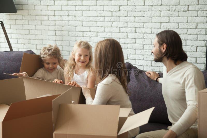 Ευτυχείς γονείς με τα παιδιά που παίζουν να ανοίξει συσκευασίας στο καθιστικό στοκ εικόνα