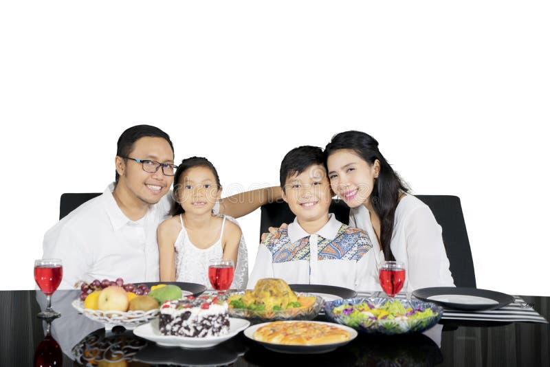 Ευτυχείς γονείς που αγκαλιάζουν τα παιδιά τους στο χρόνο μεσημεριανού γεύματος στοκ εικόνα