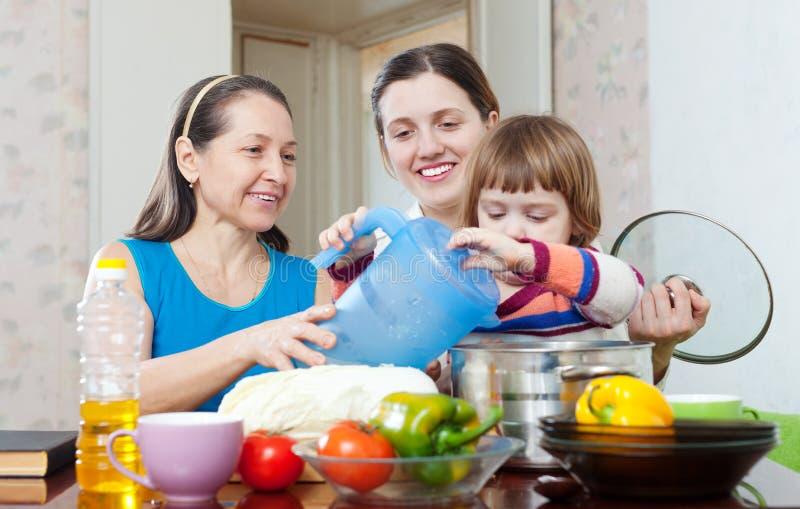 Ευτυχείς γυναίκες με το παιδί που μαγειρεύει μαζί το χορτοφάγο μεσημεριανό γεύμα στοκ εικόνες