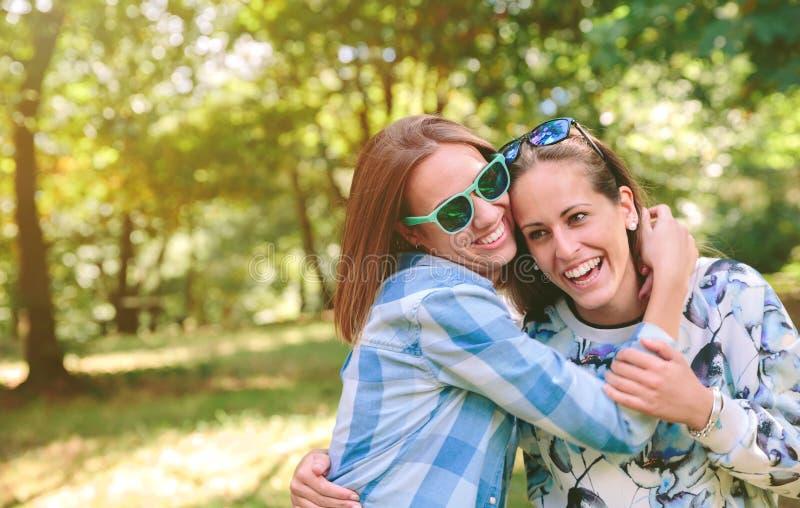 Ευτυχείς γυναίκες που αγκαλιάζουν και που έχουν τη διασκέδαση πέρα από τη φύση στοκ εικόνες