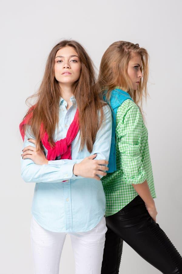 Ευτυχείς γυναίκες φίλων στα πουκάμισα και ένα πουλόβερ στους ώμους του Εικόνα άνοιξη μόδας δύο αδελφών ζωηρόχρωμα χρώματα στοκ φωτογραφίες