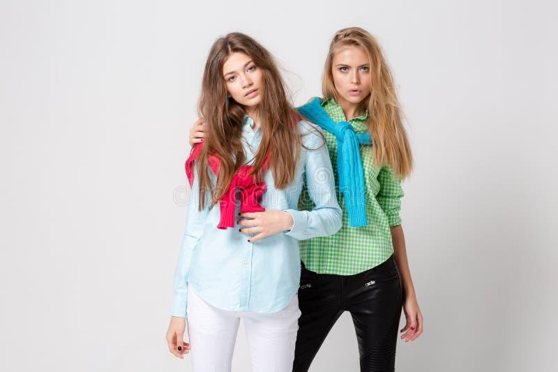 Ευτυχείς γυναίκες φίλων στα πουκάμισα και ένα πουλόβερ στους ώμους του Εικόνα άνοιξη μόδας δύο αδελφών ζωηρόχρωμα χρώματα στοκ εικόνες με δικαίωμα ελεύθερης χρήσης
