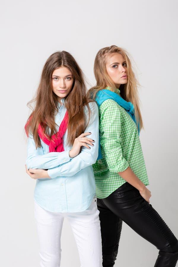 Ευτυχείς γυναίκες φίλων στα πουκάμισα και ένα πουλόβερ στους ώμους του Εικόνα άνοιξη μόδας δύο αδελφών ζωηρόχρωμα χρώματα στοκ εικόνα