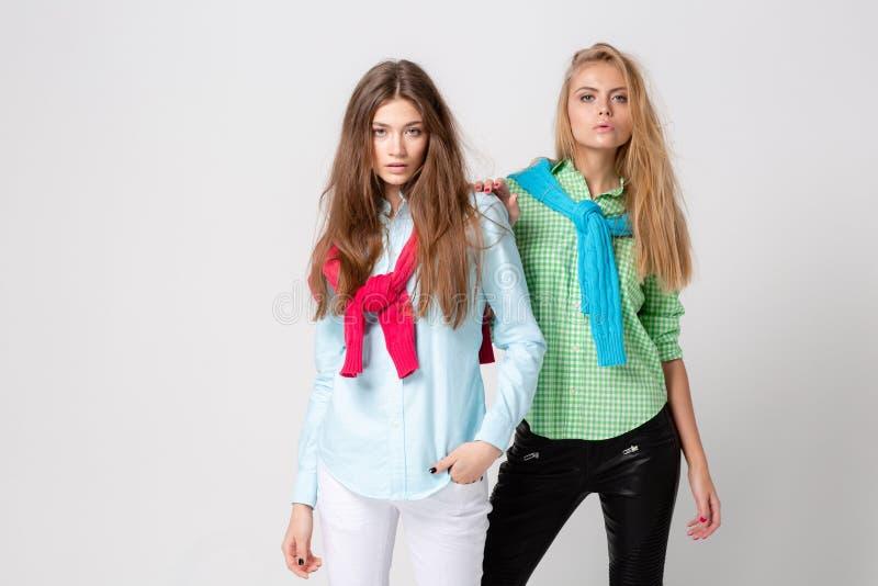 Ευτυχείς γυναίκες φίλων στα πουκάμισα και ένα πουλόβερ στους ώμους του Εικόνα άνοιξη μόδας δύο αδελφών ζωηρόχρωμα χρώματα στοκ εικόνες