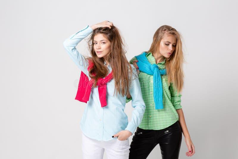 Ευτυχείς γυναίκες φίλων στα πουκάμισα και ένα πουλόβερ στους ώμους του Εικόνα άνοιξη μόδας δύο αδελφών ζωηρόχρωμα χρώματα στοκ εικόνα με δικαίωμα ελεύθερης χρήσης