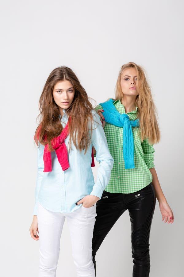 Ευτυχείς γυναίκες φίλων στα πουκάμισα και ένα πουλόβερ στους ώμους του Εικόνα άνοιξη μόδας δύο αδελφών ζωηρόχρωμα χρώματα στοκ φωτογραφία με δικαίωμα ελεύθερης χρήσης