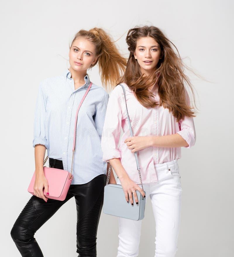 Ευτυχείς γυναίκες φίλων στα πουκάμισα με τις μοντέρνες τσάντες Εικόνα άνοιξη μόδας δύο αδελφών Ροζ και μπλε κρητιδογραφιών στοκ εικόνες