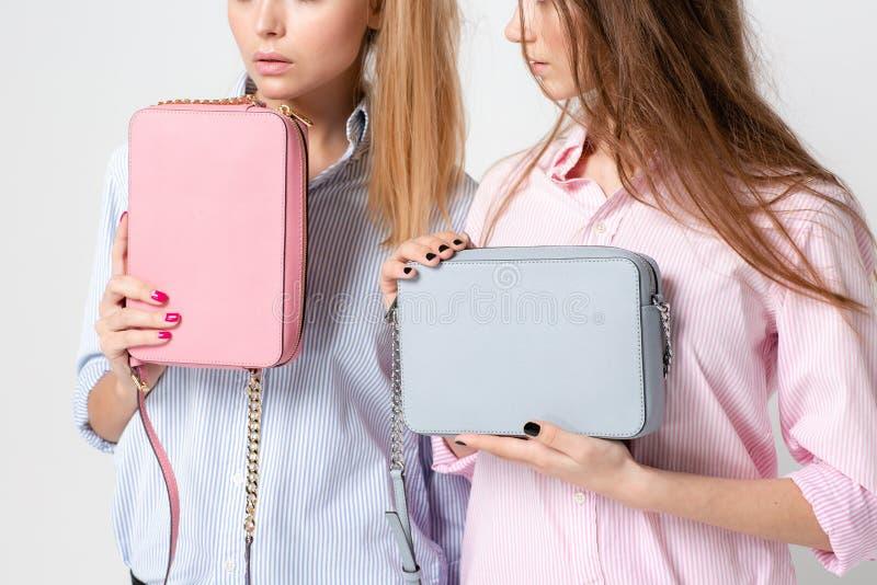 Ευτυχείς γυναίκες φίλων στα πουκάμισα με τις μοντέρνες τσάντες Εικόνα άνοιξη μόδας δύο αδελφών Ροζ και μπλε κρητιδογραφιών στοκ εικόνα