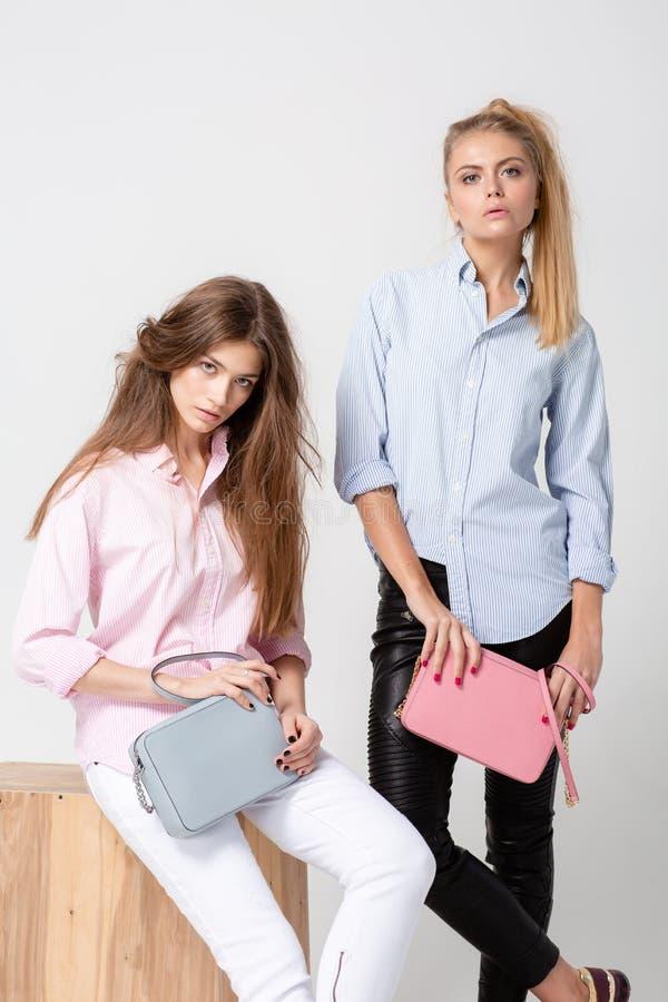 Ευτυχείς γυναίκες φίλων στα πουκάμισα με τις μοντέρνες τσάντες Εικόνα άνοιξη μόδας δύο αδελφών Ροζ και μπλε κρητιδογραφιών στοκ φωτογραφία με δικαίωμα ελεύθερης χρήσης