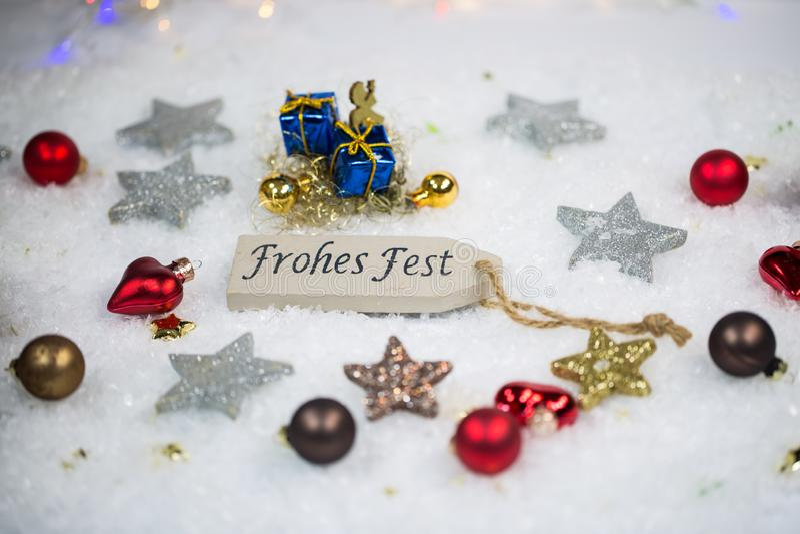 Ευτυχείς διακοπές με τις σφαίρες και τα αστέρια Χριστουγέννων στο χιόνι στοκ φωτογραφίες