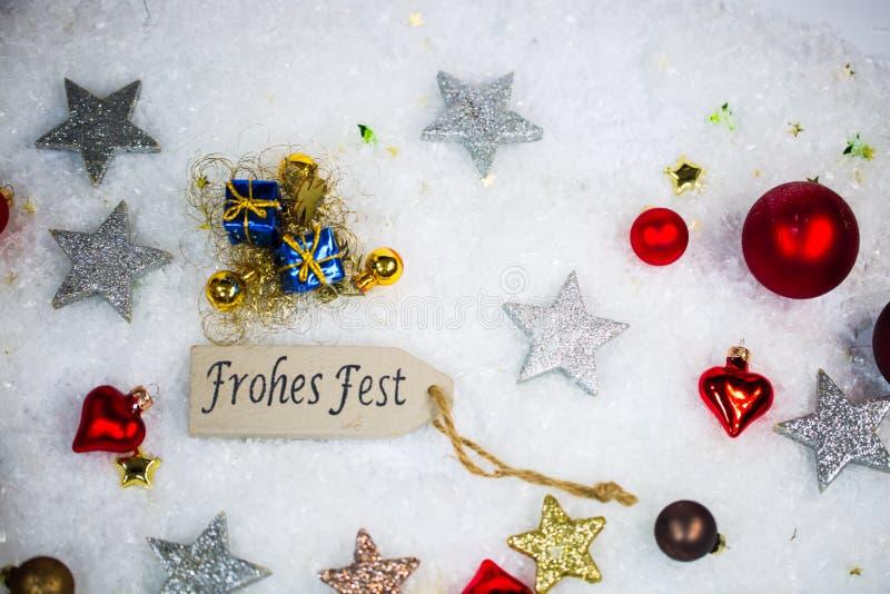 Ευτυχείς διακοπές με τις σφαίρες και τα αστέρια Χριστουγέννων στο χιόνι στοκ εικόνες