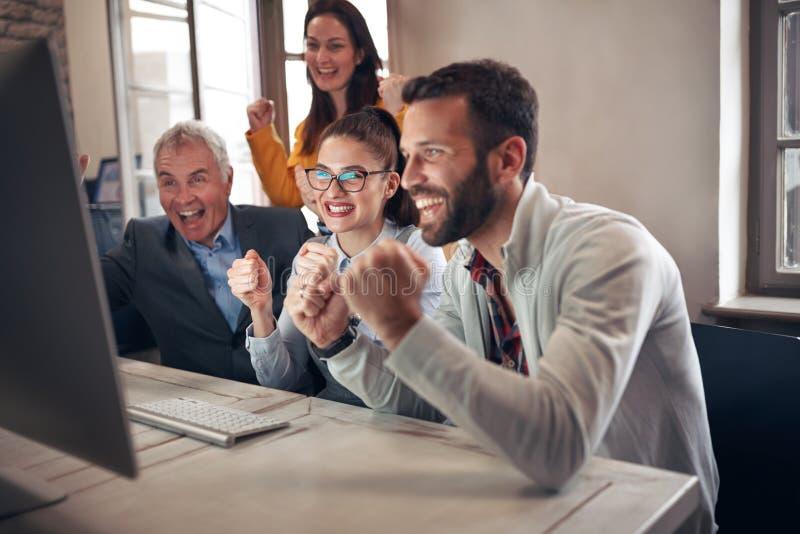 Ευτυχείς επιχειρηματίες που γιορτάζουν τα επιτυχή προγράμματα στοκ φωτογραφίες