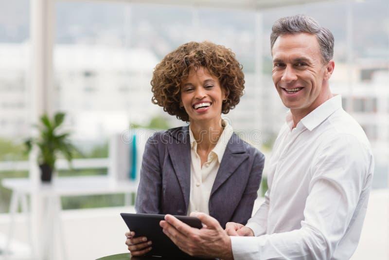 Ευτυχείς επιχειρηματίες που κρατούν μια ταμπλέτα στοκ φωτογραφία
