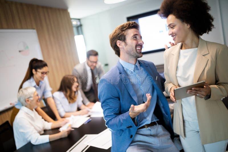 Ευτυχείς επιχειρησιακοί συνάδελφοι στο σύγχρονο γραφείο που λειτουργεί από κοινού στοκ εικόνα
