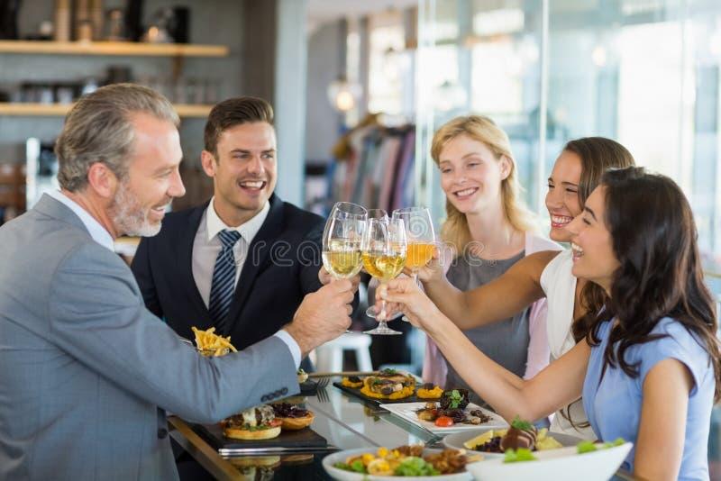 Ευτυχείς επιχειρησιακοί συνάδελφοι που ψήνουν τα γυαλιά μπύρας ενώ έχοντας το μεσημεριανό γεύμα στοκ εικόνες με δικαίωμα ελεύθερης χρήσης
