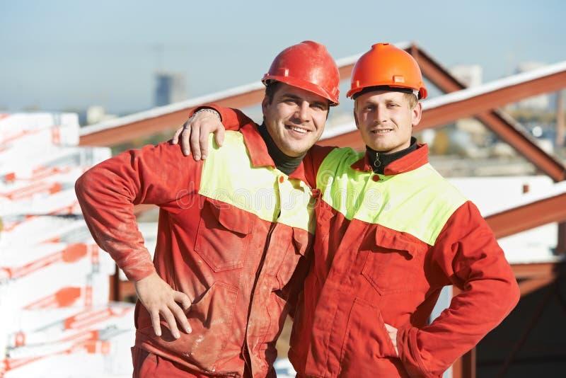 Ευτυχείς εργαζόμενοι οικοδόμων στο εργοτάξιο οικοδομής στοκ φωτογραφίες με δικαίωμα ελεύθερης χρήσης