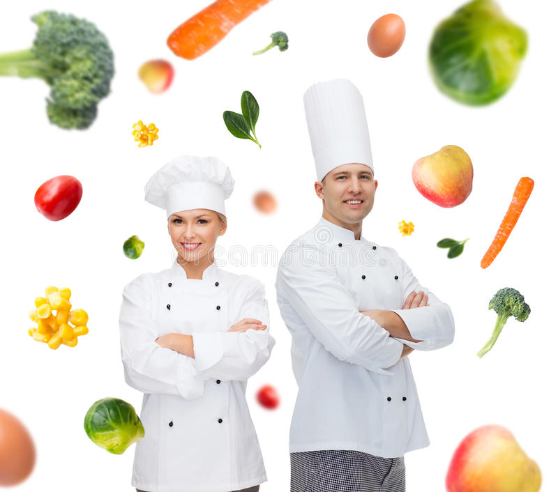 Ευτυχείς ζεύγος ή μάγειρες αρχιμαγείρων πέρα από το υπόβαθρο τροφίμων στοκ εικόνες με δικαίωμα ελεύθερης χρήσης