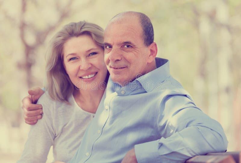 Ευτυχείς ηλικιωμένοι άνδρας και γυναίκα που αγκαλιάζουν σε έναν πάγκο στοκ εικόνες