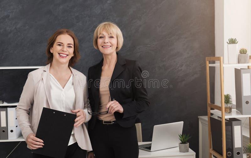 Ευτυχείς θηλυκοί συνάδελφοι στον εργασιακό χώρο στην αρχή στοκ εικόνα