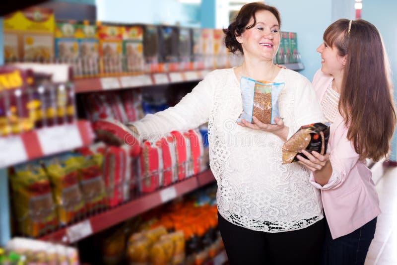 Ευτυχείς θηλυκοί αγοραστές που επιλέγουν το καφετί φαγόπυρο στο παντοπωλείο στοκ φωτογραφία με δικαίωμα ελεύθερης χρήσης