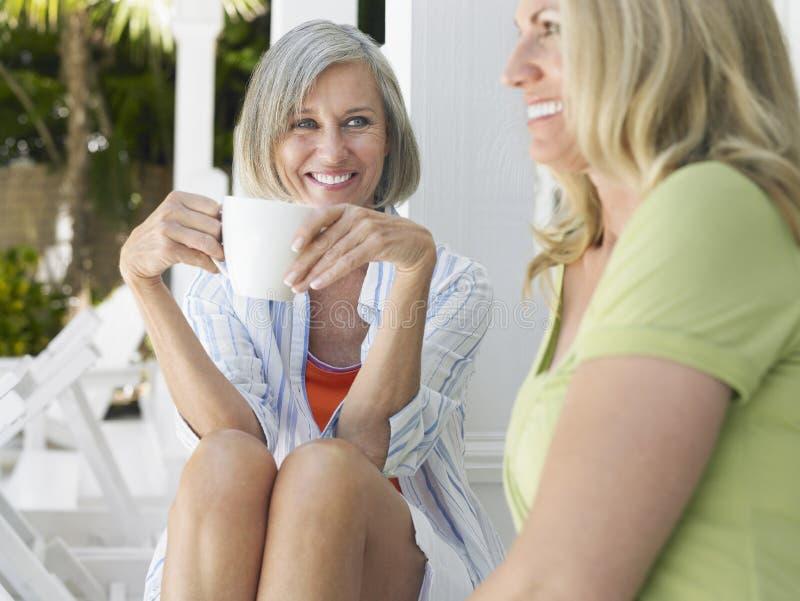 Ευτυχείς μέσες ηλικίας γυναίκες που κάθονται στη βεράντα στοκ εικόνα