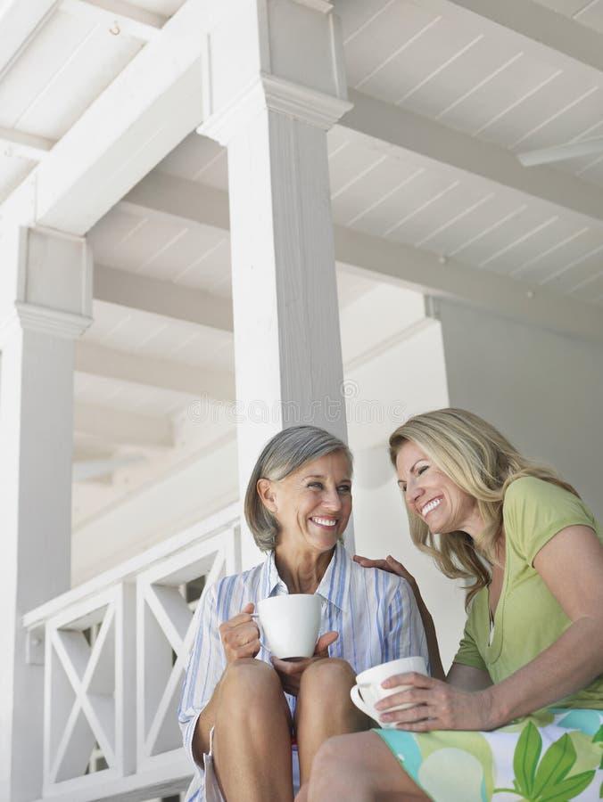 Ευτυχείς μέσες ηλικίας γυναίκες στη βεράντα με τα φλυτζάνια στοκ εικόνες