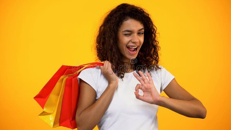 Ευτυχείς μαύρες θηλυκές τσάντες αγορών εκμετάλλευσης και παρουσίαση εντάξει χειρονομίας, κλείσιμο του ματιού στοκ φωτογραφία