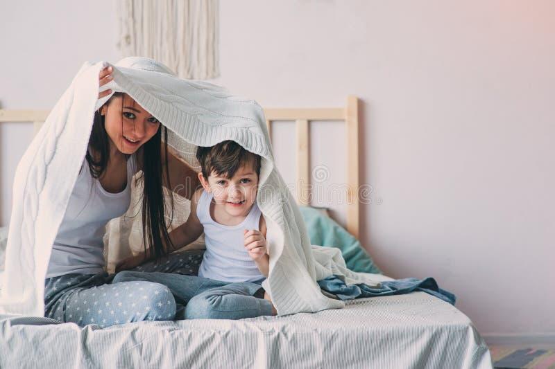 Ευτυχείς μητέρα και γιος που παίζουν και που κρύβουν κάτω από το κάλυμμα στο κρεβάτι το άνετο πρωί Σαββατοκύριακου στοκ εικόνες
