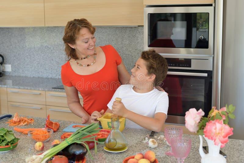 Ευτυχείς μητέρα και γιος που προετοιμάζουν το μεσημεριανό γεύμα με ένα κονίαμα στοκ φωτογραφία