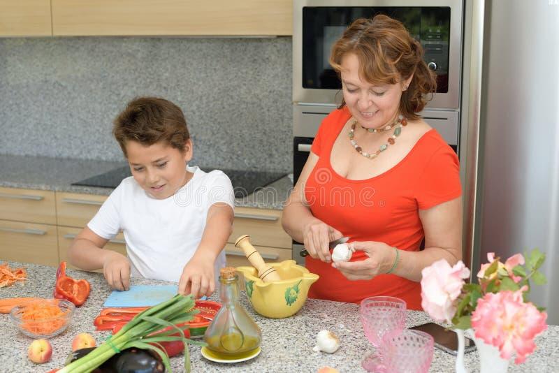 Ευτυχείς μητέρα και γιος που προετοιμάζουν το μεσημεριανό γεύμα στην κουζίνα στοκ φωτογραφία με δικαίωμα ελεύθερης χρήσης