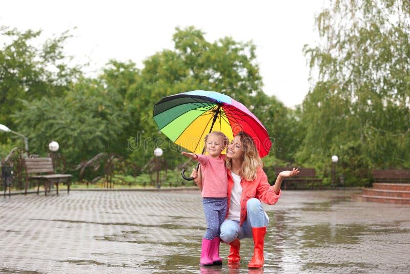 Ευτυχείς μητέρα και κόρη με τη φωτεινή ομπρέλα κάτω από τη βροχή στοκ εικόνες