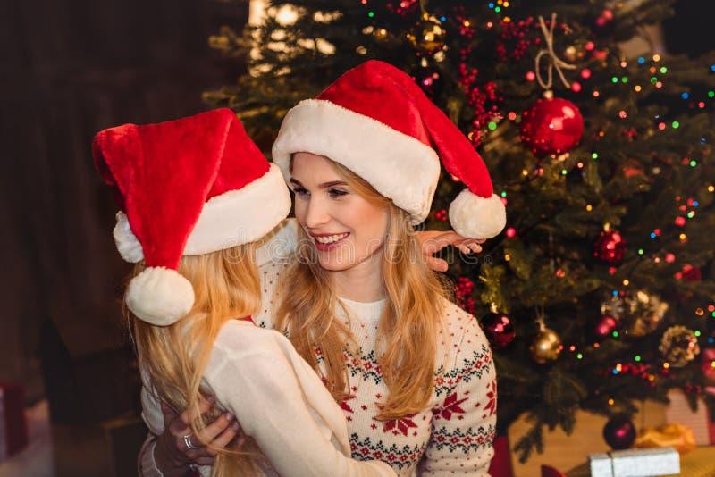 Ευτυχείς μητέρα και κόρη που αγκαλιάζουν κάτω στοκ εικόνες