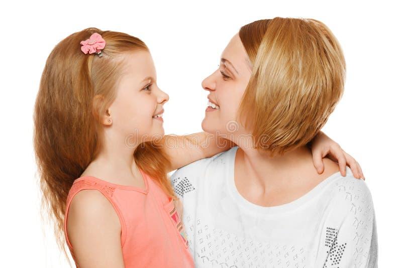 Ευτυχείς μητέρα και κόρη που αγκαλιάζουν και που εξετάζουν η μια την άλλη, που απομονώνεται στο άσπρο υπόβαθρο στοκ εικόνες
